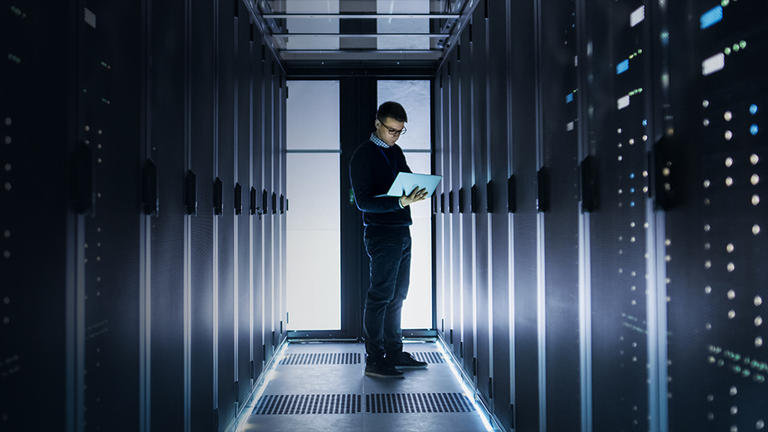 Male IT Engineer Works on a Laptop at the end of a Corridor in a Big Data Center. Rows of Rack Servers are Seen.
